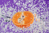 Orange (mandarin) floating in water — Stock Photo