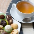 Cap of tea and sweets plate — Stock Photo