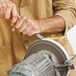 Manual worker sharp his tool - Stock Photo