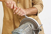 Manual worker sharp his tool — Stock Photo