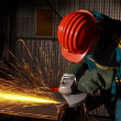 Foto Stock: Heavy industry manual worker with grinde