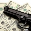 Pistol and dollar — Stock Photo
