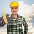 Smiling handyman and building background — Stock Photo #2504909