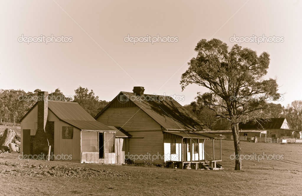 An old house of a cattle station or ranch in the middle of the field in sepia — Stock Photo #1865634