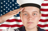 Young sailor saluting in front of US flag — Stock Photo