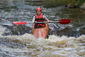 Teenage girl white water kayaking — Stock Photo
