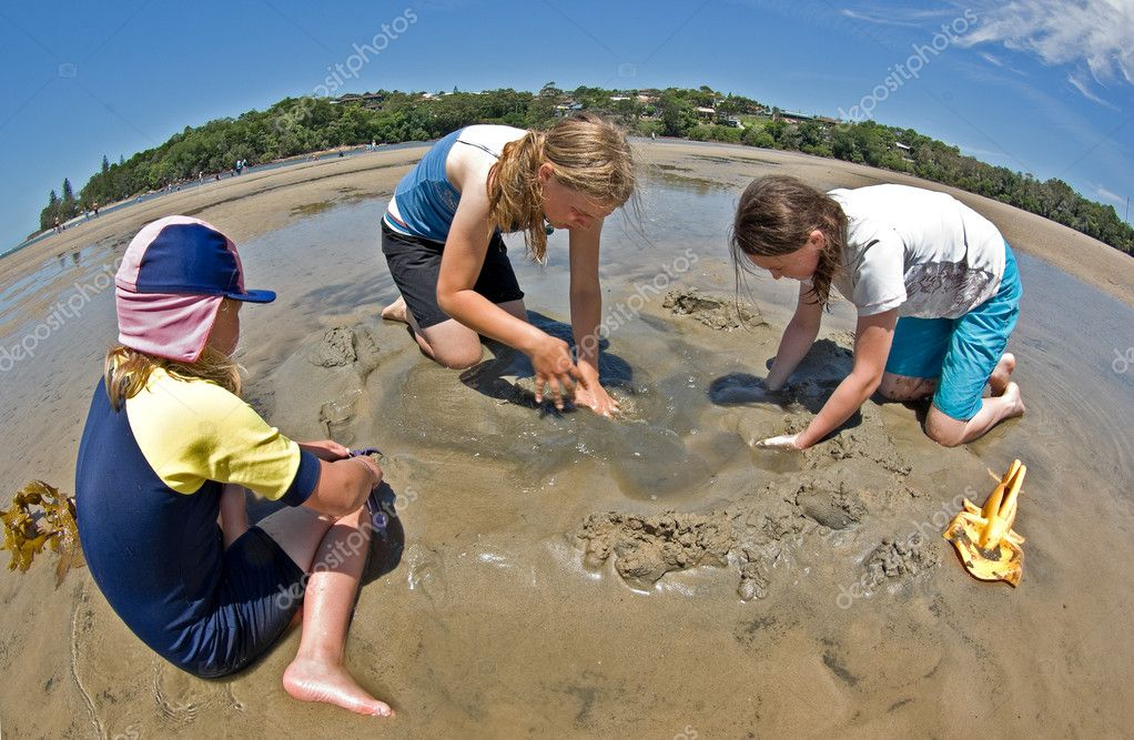 Three girls digging and bulding sand castles at the beach  Stock Photo #2063646