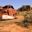 Stock Photo: Old rusting car and desert ruins