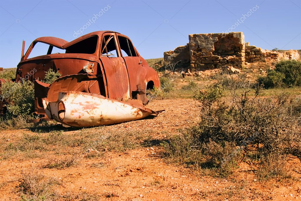 An old rusting car and ruins
