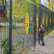 A child stands at the closed gates — Stock Photo