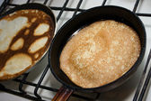 Pancakes are fried in a pan — Stock Photo