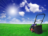 Lawn mower on green field — Stock Photo