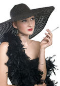 Women in black hat and boa with a cigare — Stock Photo
