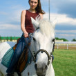 Royalty-Free Stock Photo: Girl astride a horse against blue sky