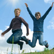 Men jumping against summer landscape — Stock Photo