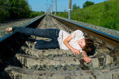 Girl laying on a railway — Stock Photo