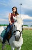 Girl astride a horse against blue sky — Stock Photo