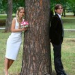 Bride and groom against urban park — Stock Photo