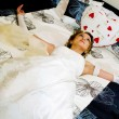 Royalty-Free Stock Photo: Bride in a wedding dress lies on a bed