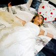 Bride in a wedding dress lies on a bed - Stock Photo