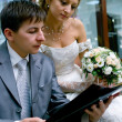 Bride and groom reading the magazine — Stock Photo