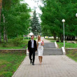 Bride and groom against urban park - Stock Photo