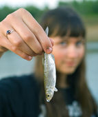 Girl holds the first caught fish in a ha — Stock Photo