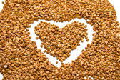Heart on buckwheat groats — Stock Photo