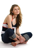 Girl in jeans sits on a white — Stock fotografie