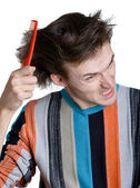 Young man with the hairbrush — Stock Photo