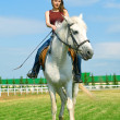 Stock Photo: Smiling girl embraces a white horse