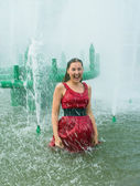 Girl in wet clothes in a city fountain — Stock Photo