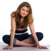 Mädchen in Jeans sitzt auf einem weißen — Stockfoto