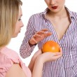 Girl offers the girlfriend a grapefruit — Stok fotoğraf