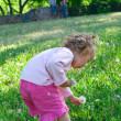 Stock Photo: Little girl plays with flowers