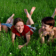 Stock Photo: Girls lay in a green grass