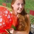 Smiling girl with a red balloon — Stock Photo