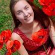 Girl with long hair in poppies field - Stock Photo
