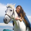 Beautiful girl embraces a white horse — Stock Photo