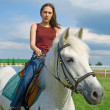Stock Photo: Girl astride horse against blue sky