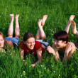 Girls lay in a green summer grass — Stock Photo