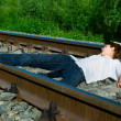 Young girl laying on a railway — Stock Photo