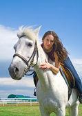 Linda garota abraça um cavalo branco — Fotografia Stock