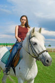 Girl astride a horse against blue sky — Stock Photo