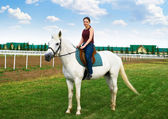 Smiling young girl astride a horse — Stock Photo