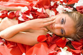 Young girl in rose petal — Stock Photo