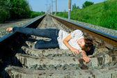 Girl laying on a railway — Stock Photo