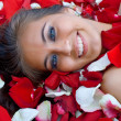 Smiling young girl in rose petal — Stock Photo