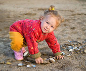 Little girl plays with cockleshells — Stock Photo