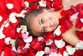 Beautiful young girl in rose petal — Stock Photo